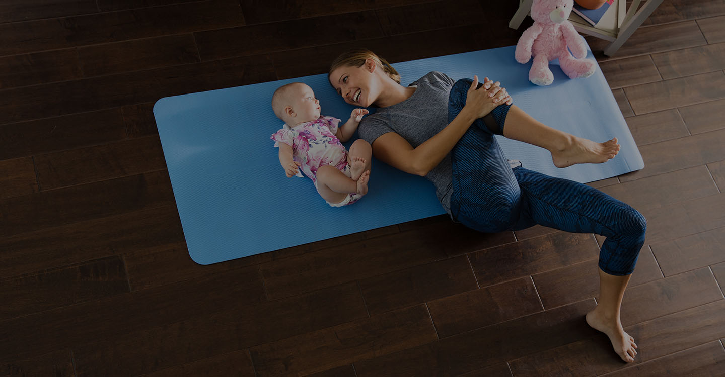 Mother and baby stretching on a yoga mat