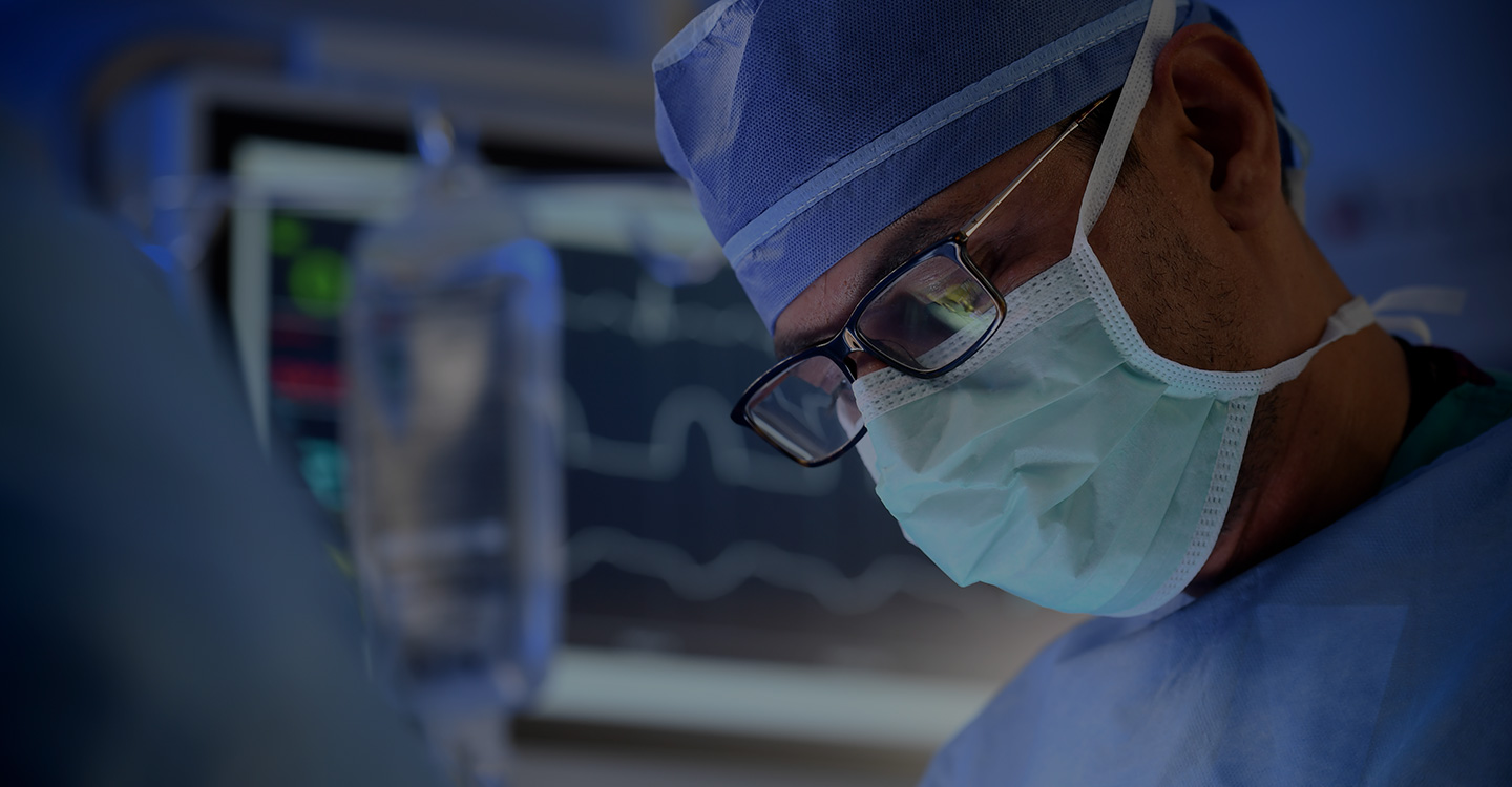 Surgeon looking down while conducting a surgery