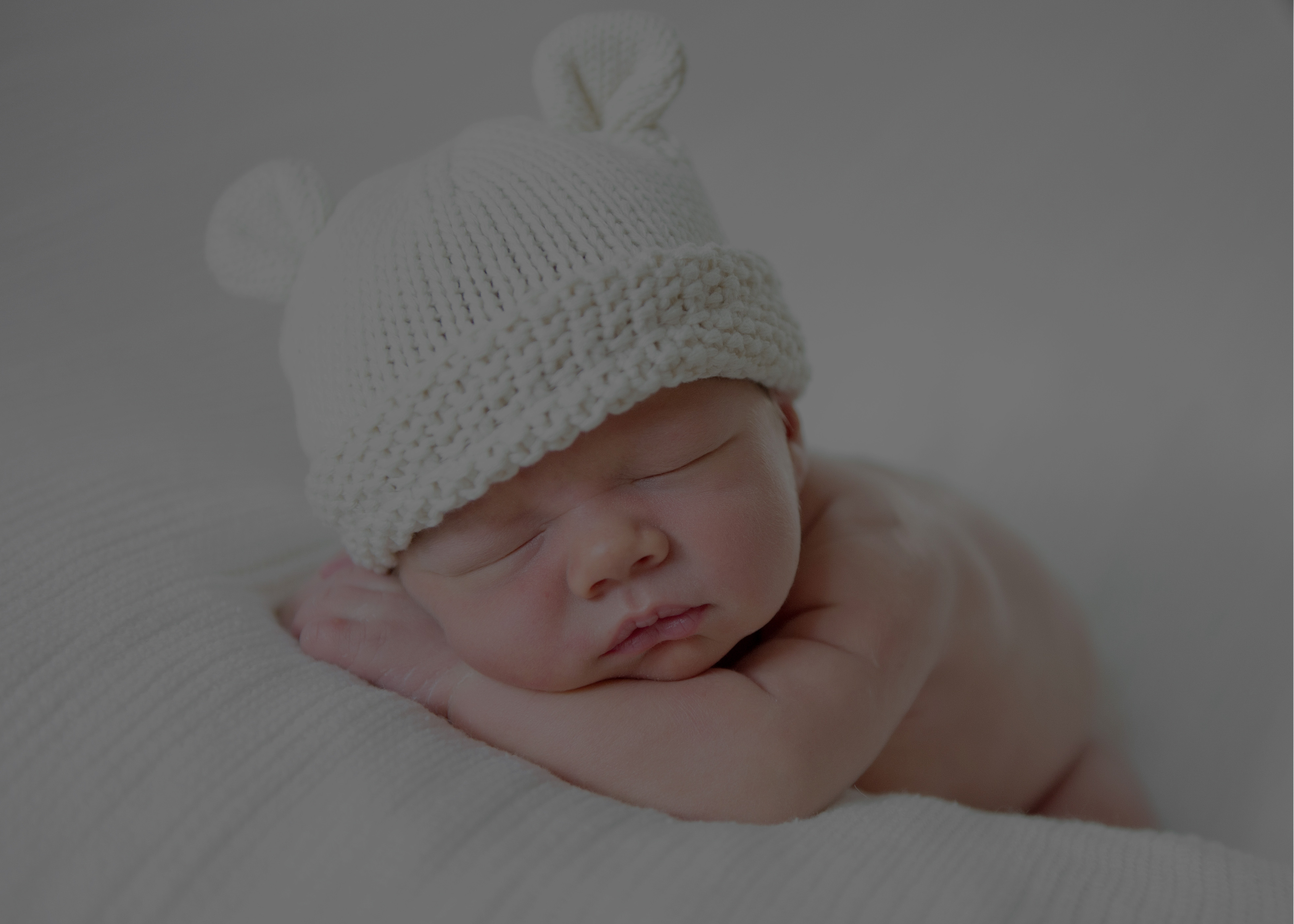 New born baby sleeping with a white hat